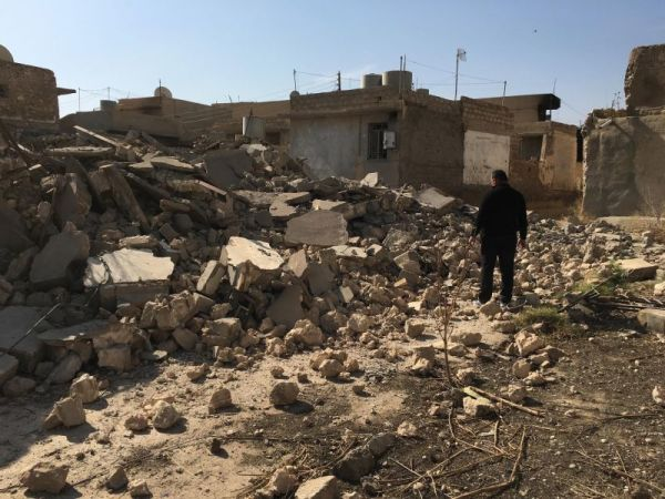 Father Thabet Habib inspects damage in the town of Karamles, Iraq right after the town was liberated from the Islamic State in October 2016.